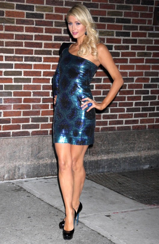 Paris Hilton in a short and tight blue dress and high heels
